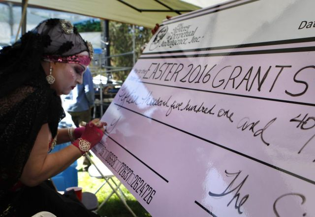 Sister Kristian signs a check for over $15,000 dollars in Grant money during the 37th annual Easter in the Park celebration put on by the Sisters of Perpetual Indulgence in San Francisco, Calif., on Sunday March 27, 2016. Photo: Brittany Murphy, The Chronicle